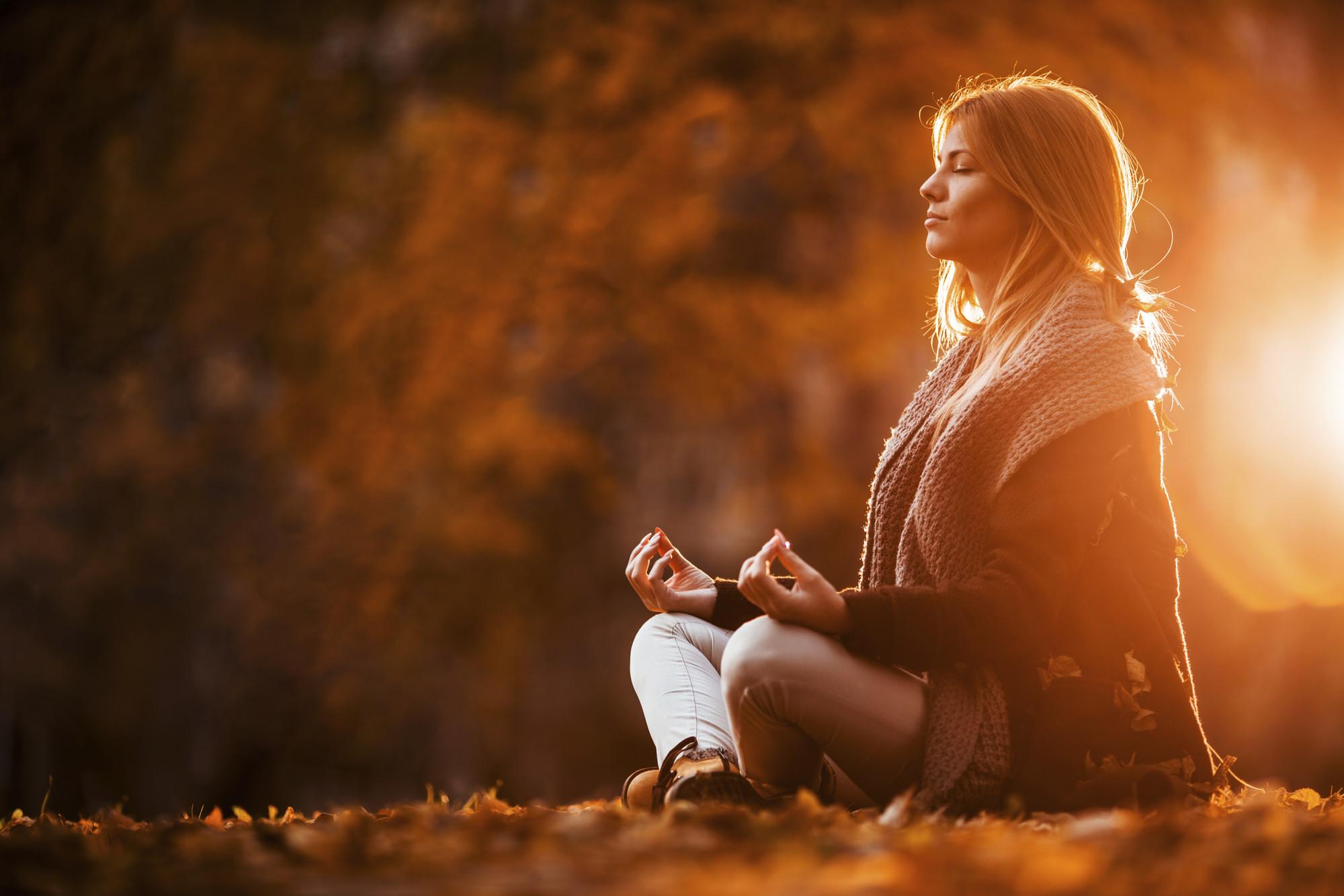 Ung kvinna mediterar i höstsolen