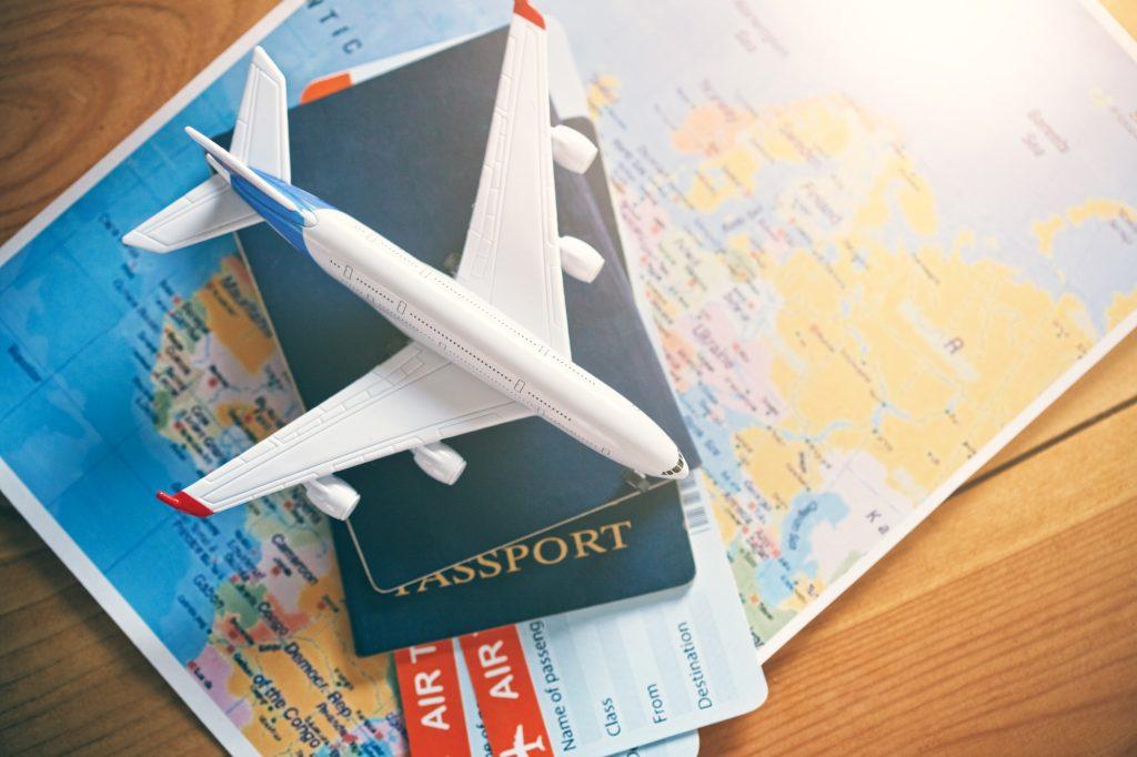 Litet flygplan, resepass, biljetter och karta över världen för din nästa resa med våra Covid-19 resetips
