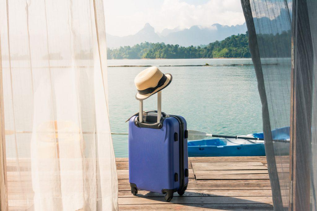 Resväsken står på terrassen vid sjön efter ankomst till hotellet.