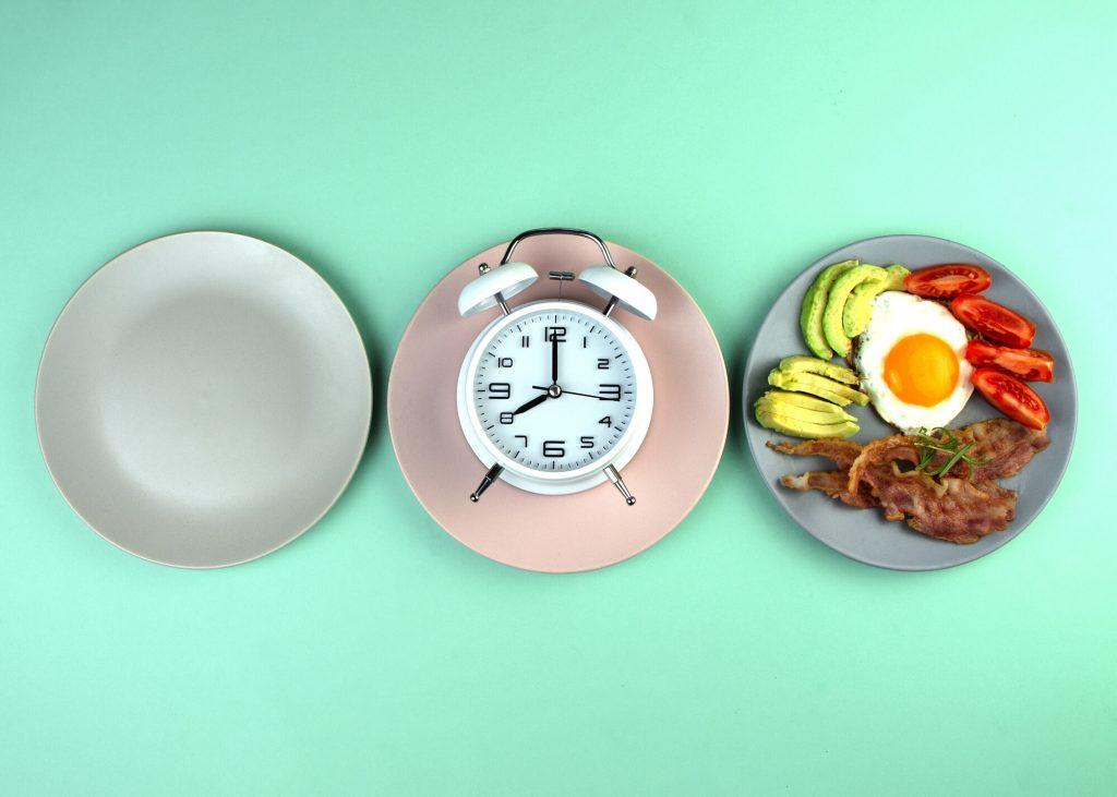 Periodisk fasta för hälsan - Tre tallrikar: en tom, en med en väckerklocka på och en med skinka, ägg, avokado och tomater.