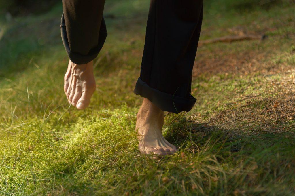 En människas blotta fötter vandrar försiktigt över mjuk mossa i skogen.