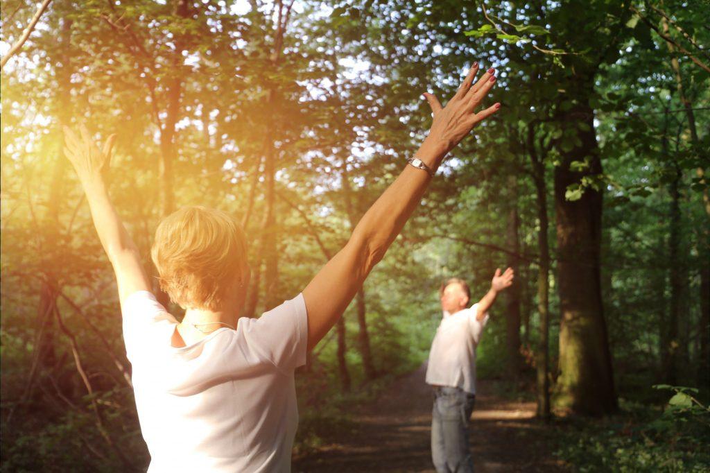 Äldre par njuter med att skogsbada. Solen ger ett varmt ljus.