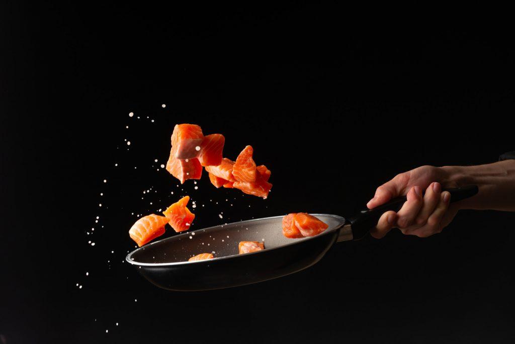 laxbitar kastas upp från en pannan - pegan-dieten tillåter fisk