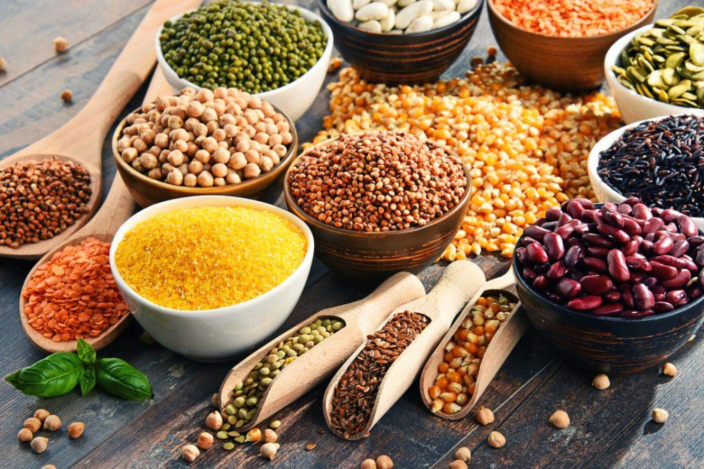 trädskedar och skålar med färgglada frön, nötter och baljväxter för pegan-dieten