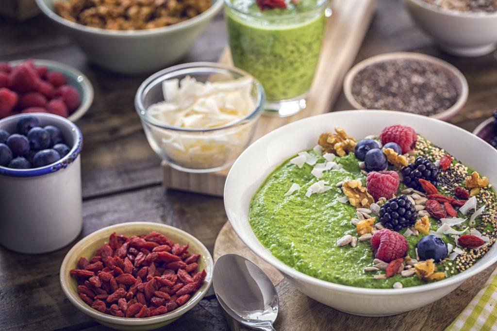 frukt, kokosgryn, nötter, frön och muesli i skålar för pegan kosthållning