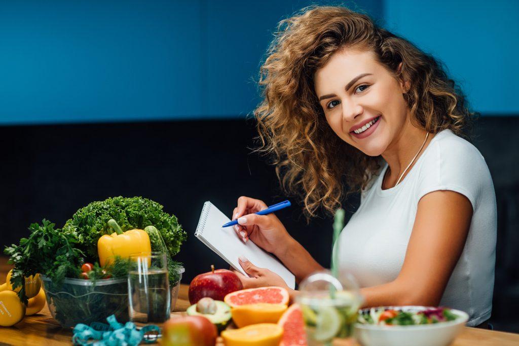 ung kvinna sitter med block och penna vid ett bod med grönsaker och frukt som passar för pegan-dieten