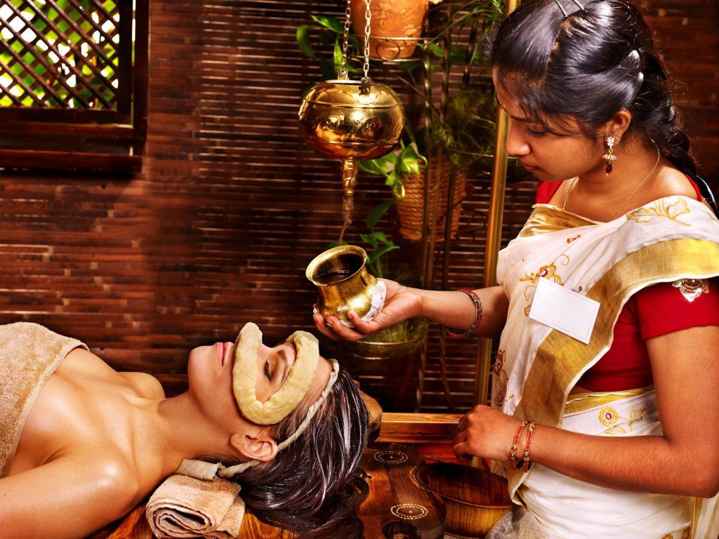 kvinna får en traditionell Ayurveda behandling, olja hälls i en degring runtomkring ögonen