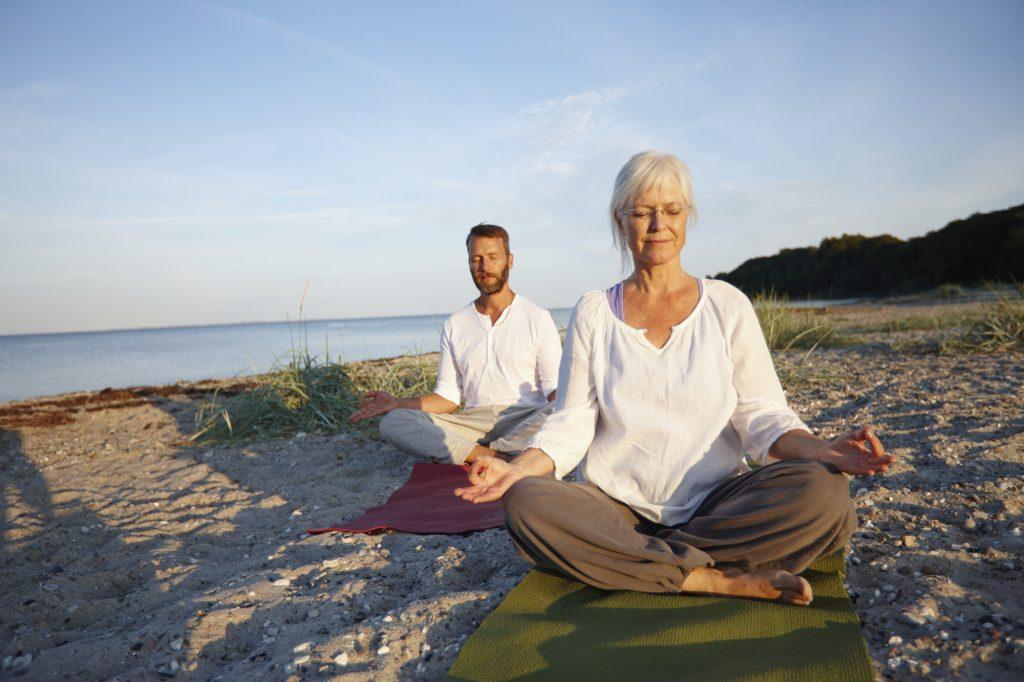 Äldre par praktiserar Yoga på stranden nära vattnet - Ayurveda och Yoga för viktminskning