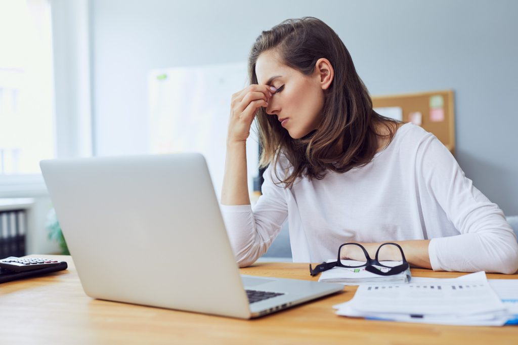 En ung kvinna sitter framför datorn, ser stressad ut och håller sig för huvudet pga smärta.