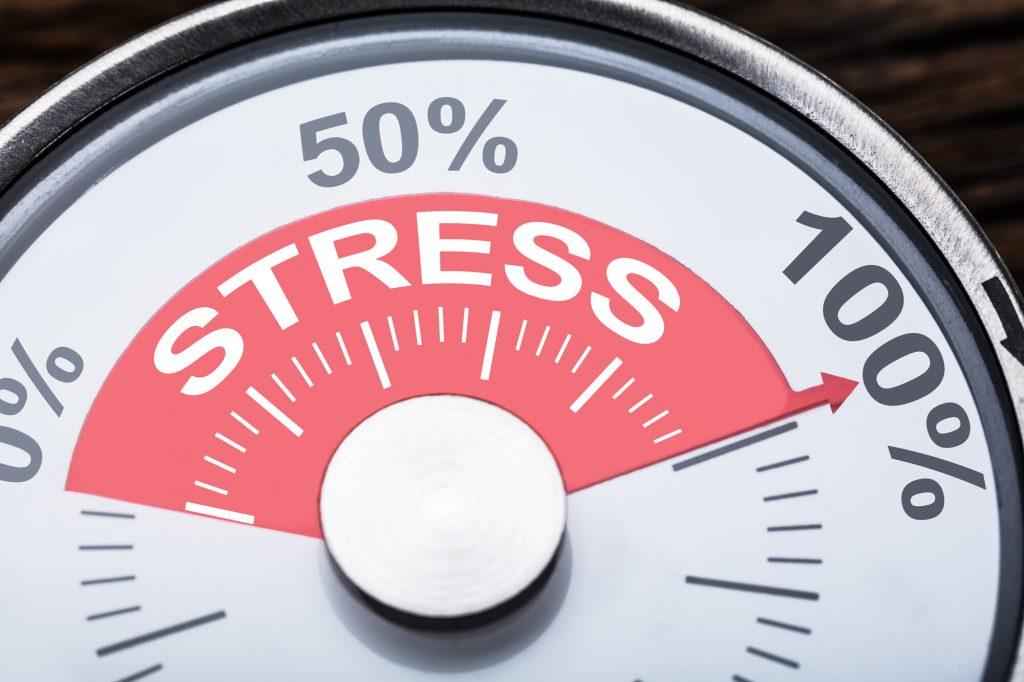 """Närbild av ordet """"stress"""" med siffror och procenttecken på mätinstrumentet."""